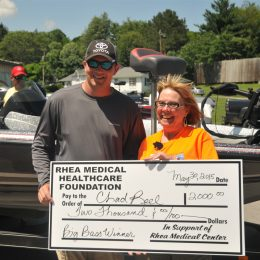 Chad Reel from Dayton, holds symbolic $2000 check for the Chickagauga Big Bass Fishing Fundraiser on May 30, 2015.  Becky Bodkin from Rhea Medical Foundation and Tournament Director presents the check.(Photo:GaryBolden/RheaReview)